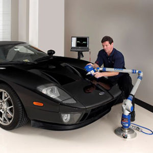An employee is 3d scanning a car.